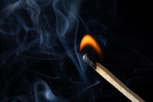 Uma fotografia macro de um palito de fósforo iluminado com um pouco de fumaça e fogo