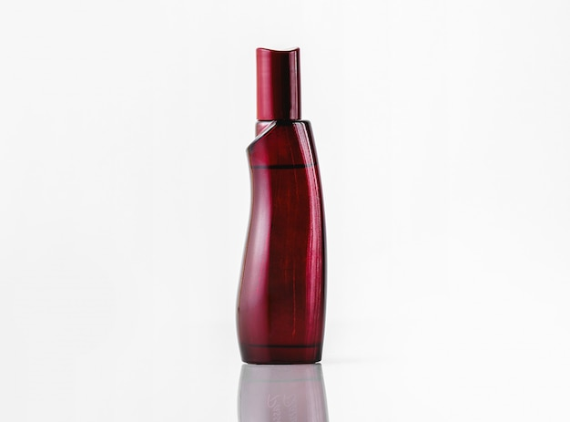 Uma fragrância de garrafa vermelha escura vista frontal isolada na mesa branca