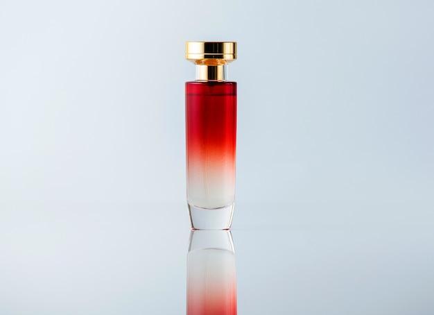 Uma fragrância de vista frontal branca e vermelha projetada transparente na mesa de luz