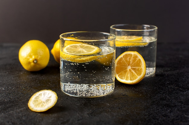 Uma frente fechou a água de vista com bebida fresca de limão com limões fatiados dentro de vidros transparentes