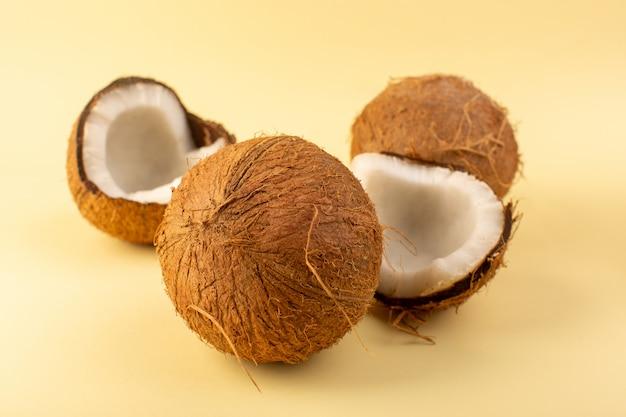 Uma frente fechou a vista cocos maduro fresco leitoso isolado no fundo colorido creme porca de frutas exóticas tropicais