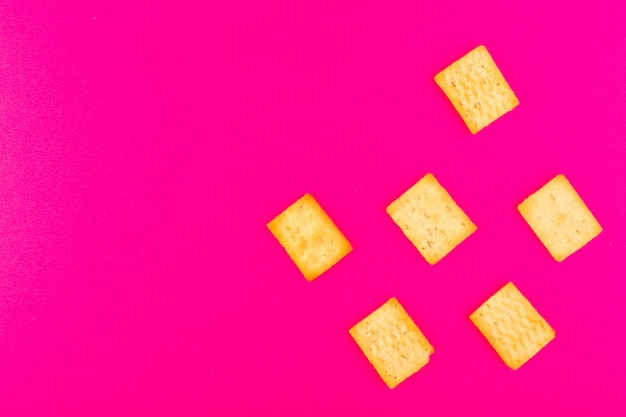 Uma frente fechou a vista salgados biscoitos salgados queijo cracking isolado no fundo rosa lanche cracker