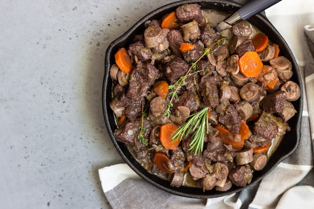 Uma frigideira com bourguignon de carne com salsichas, cenouras, alho, cebola, vinho tinto, ervas e especiarias.