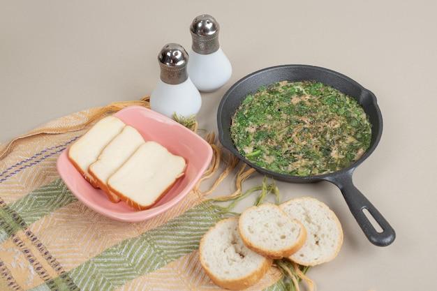 Uma frigideira escura com omelete, verduras e pão branco fresco.