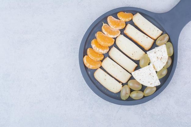 Uma frigideira escura com pão fatiado e frutas.