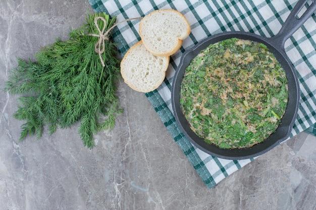 Uma frigideira escura de ovos fritos com verduras e pão branco na toalha de mesa. foto de alta qualidade