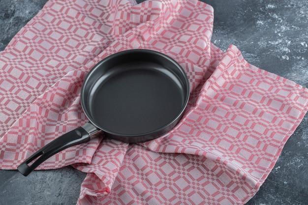 Uma frigideira preta vazia sobre uma toalha de mesa.