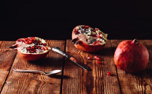 Uma fruta de romã recém-aberta com faca e colher vintage