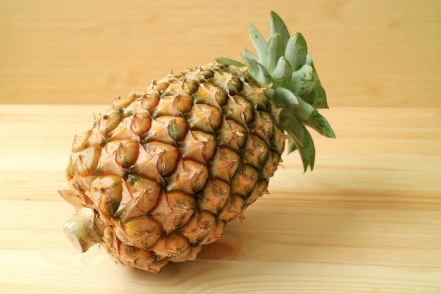 Uma fruta inteira madura fresca do abacaxi isola-se no fundo de madeira