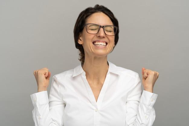 Uma funcionária de escritório bem-sucedida vitoriosa e alegre que levanta os punhos celebra a promoção ou recompensa na carreira, estando feliz por alcançar seu objetivo