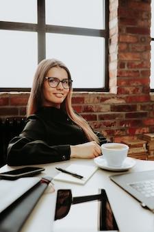 Uma funcionária de sucesso no escritório com uma xícara de café
