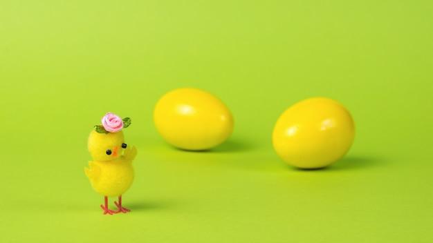 Uma galinha amarela com uma flor no fundo de dois ovos amarelos.