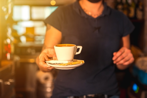 Uma garçonete com uma xícara de café descafeinado branco entregando-o a um cliente