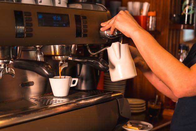 Uma garçonete em uma máquina de café colocando um descafeinado em uma xícara branca