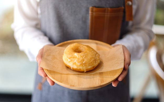 Uma garçonete segurando e servindo um pedaço de rosquinha caseira na bandeja de madeira