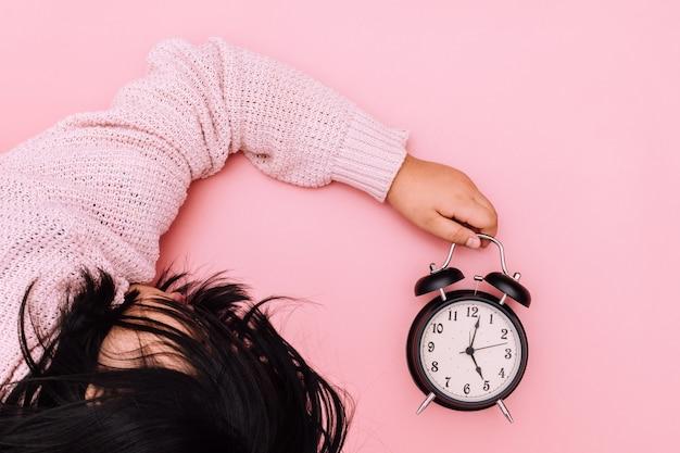 Uma garota adormecida segurando um despertador em um fundo rosa