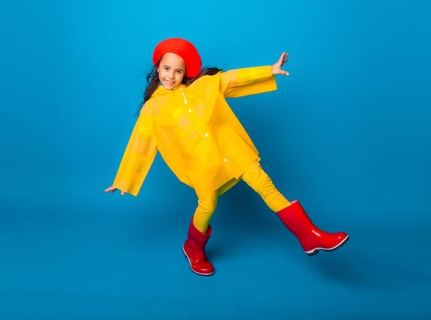 Uma garota alegre com uma capa de chuva amarela e botas de borracha vermelhas pula com os braços estendidos e olha para a câmera.