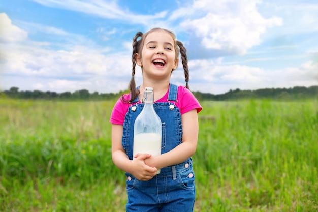 Uma garota alegre e sorridente com rabo de cavalo, de macacão jeans e uma camiseta rosa, segura uma garrafa de vidro de leite no verão, em um campo na grama. céu azul com nuvens.