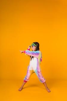Uma garota alegre em um pijama de pelúcia com óculos grandes aponta a mão para o lado em um fundo amarelo com um lugar para texto