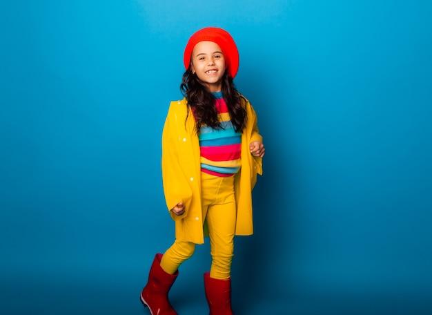 Uma garota alegre em uma capa de chuva amarela, boina vermelha e botas de borracha pula com os braços estendidos e olha para a câmera.