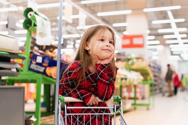 Uma garota alegre segura um carrinho e seleciona produtos para casa. o conceito de fazer compras no supermercado, seleção de produtos, vendas