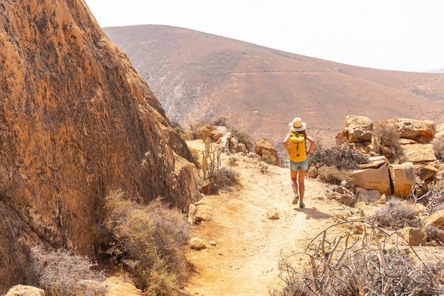 Uma garota alpinista com uma mochila amarela na trilha mirador de la peñitas no cânion peñitas, fuerteventura, ilhas canárias. espanha