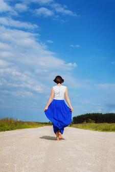 Uma garota andando na estrada. o conceito de estilo de vida, viajar.