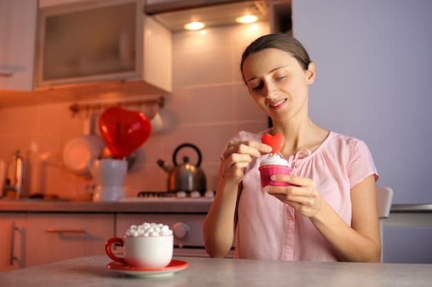 Uma garota apaixonada prepara cupcakes para um ente querido no dia dos namorados, decorando a sobremesa com um coração. uma bela e deliciosa declaração de amor.