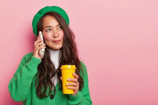 Uma garota asiática de aparência agradável e sonhadora segura o smartphone perto da orelha, conversa agradável enquanto bebe café para viagem, tem longos cabelos escuros, vestida com roupas verdes elegantes