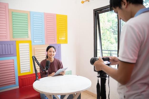 Uma garota asiática usando um tablet e um microfone enquanto um podcast está sendo gravado na câmera