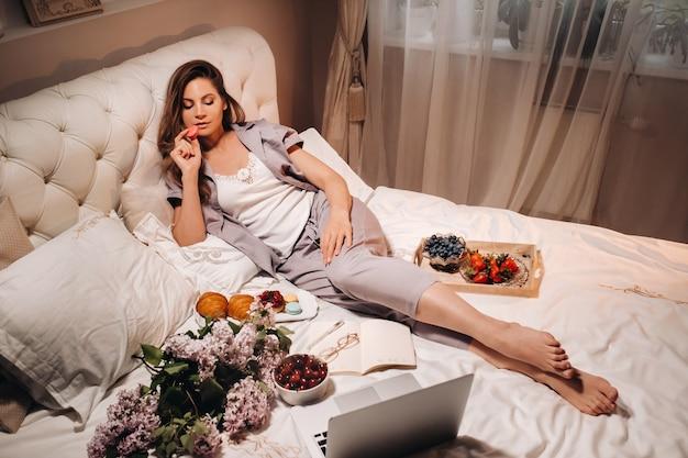 Uma garota assistindo a um laptop e comendo morangos