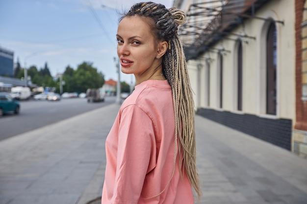 Uma garota atraente com longos cabelos loiros se ergue na rua da cidade e misteriosamente parece ...