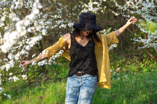 Uma garota atraente com um chapéu entre árvores florescendo aprecia o cheiro das flores da primavera.