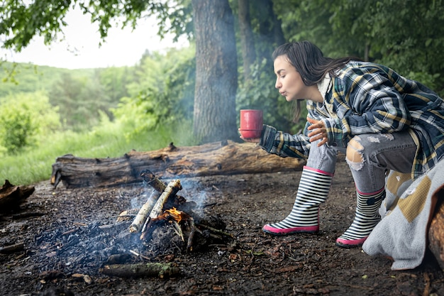 Uma garota atraente com uma xícara na mão se aquece perto de um incêndio na floresta.