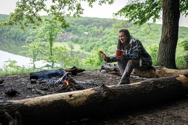 Uma garota atraente com uma xícara na mão se senta em um tronco e se aquece perto de uma fogueira na floresta.