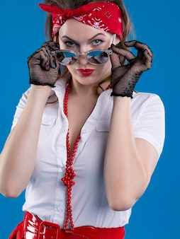 Uma garota atraente de pin-up com uma bandana vermelha na cabeça olha atentamente para os óculos baixos