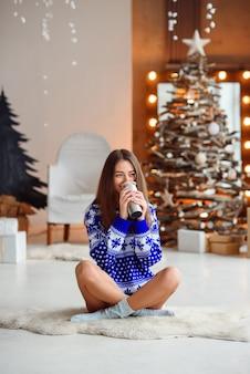 Uma garota atraente e sorridente com um suéter azul do ano novo senta-se em um tapete branco quente com uma garrafa térmica