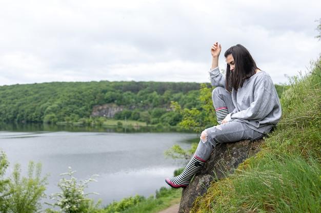 Uma garota atraente em uma caminhada escalou um penhasco em uma área montanhosa e aprecia a paisagem.