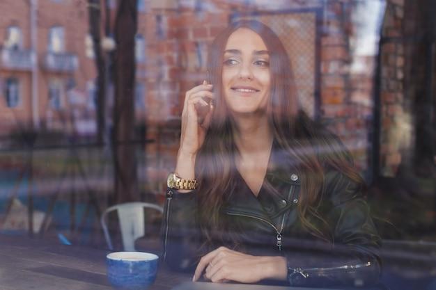 Uma garota atraente em uma jaqueta de couro, falando em um telefone celular e sorrindo fora de um café.
