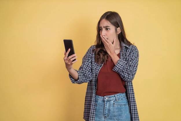 Uma garota atraente se surpreende ao ver uma tela de celular com copyspace