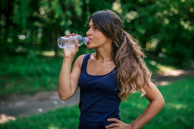 Uma garota bebe água depois do esporte