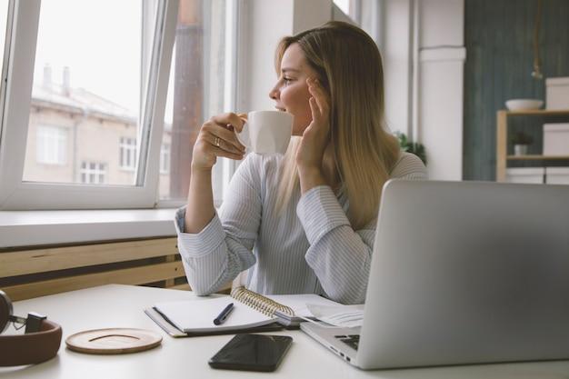 Uma garota bebe café em sua mesa