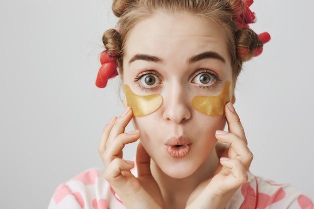 Uma garota boba e fofa com bobes de cabelo e pijamas com tapa-olhos