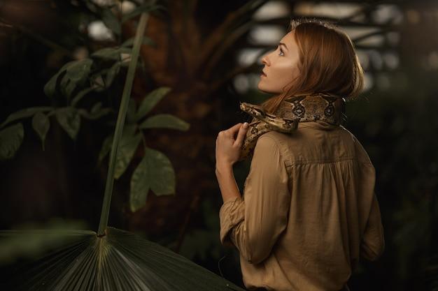 Uma garota bonita com maquiagem natural e cabelo vermelho fica na selva entre plantas exóticas com cobra.