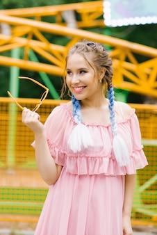 Uma garota bonita com tranças azuis e maquiagem profissional rosa e lilás brilhante está segurando um par de óculos de sol de aro amarelo e sorrindo um sorriso deslumbrante