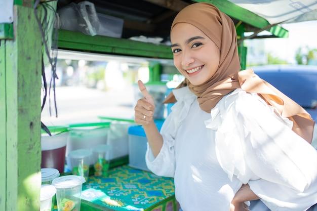 Uma garota bonita com um véu vendendo frutas geladas sorri feliz com um polegar para cima