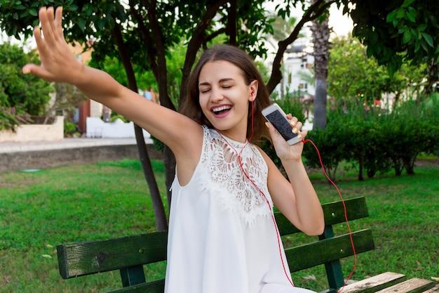 Uma garota bonita de vestido branco está ouvindo sua música favorita no banco do parque. ela gosta e está se divertindo