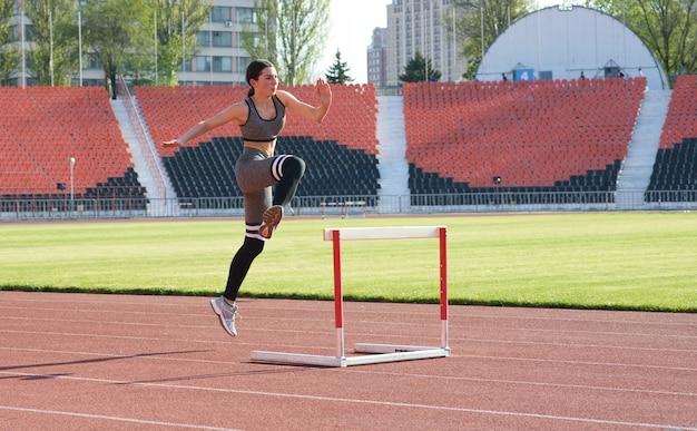 Uma garota bonita e atlética está correndo com barreiras no estádio