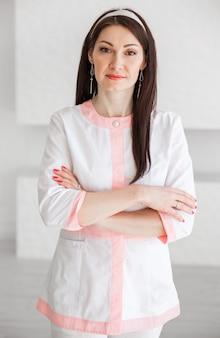 Uma garota bonita e bonita em um terno médico leve, com os braços cruzados, posando em um fundo branco. a garota olha para a câmera.