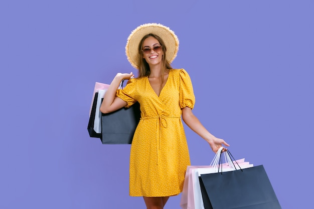 Uma garota bonita e caucasiana carrega roupas enquanto segura pacotes com fundo roxo. grandes vendas